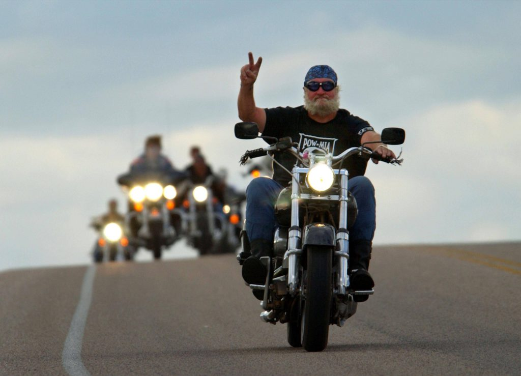 392973 16: A motorcylist gives a hand signal while on a run near Devils Tower National Monument, WY which is one of many popular destinations for cyclists attending the 61st annual Sturgis Motorcycle Rally, August 8, 2001, held in Sturgis, SD. (Photo by David McNew/Getty Images)