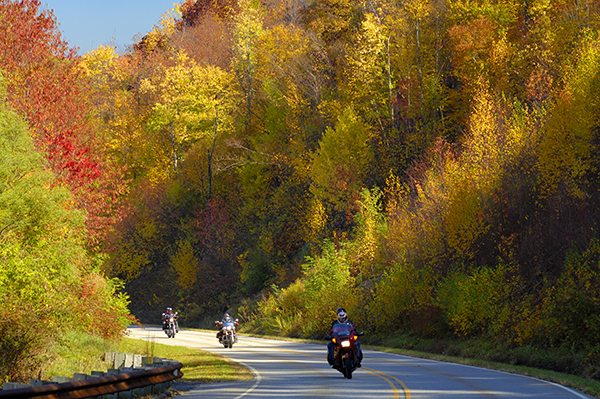 Motorcyclists on Cherohala Skyway in late October at the peak of the Autumn leaf color season. This National Scenic Byway runs between Tellico Plains, Tennessee and Robbins, North Carolina, USA.  It is traveled by many motorcycle drivers because of its scenic beauty and low traffic volume in comparison to other natural areas.