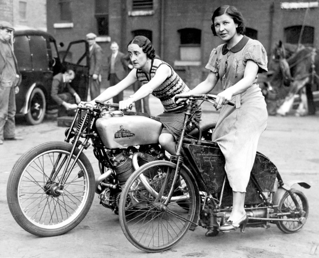 Two women astride an 1895 Crank Drive motorcycle, right, and a 500 New Imperial Twin, left, which has reached 114mph at Brooklands.